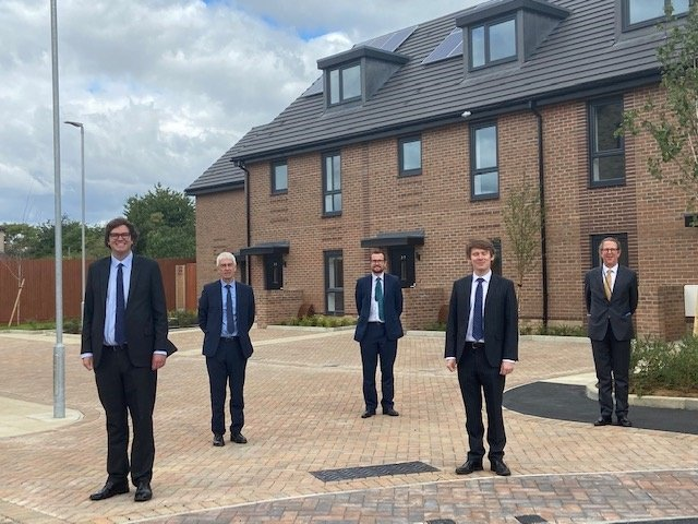Havering council members standing outside of new houses in Romford